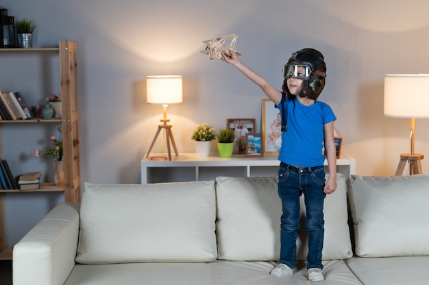 Little girl child child plays in a helmet and glasses