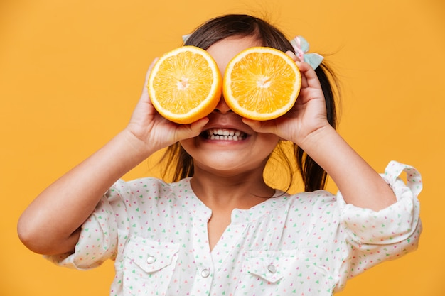 Little girl child covering eyes with orange.
