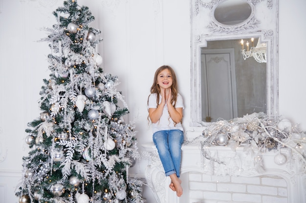 Little girl child decorating christmas tree in white classic interior sitting on a fireplace with mirror. merry christmas, happy new year, happy holidays.