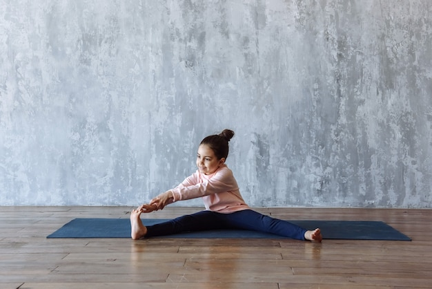 매트에 앉아 바닥에 스트레칭과 체조를 하 고 어린 여자 아이
