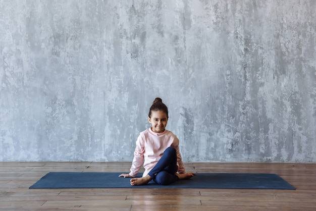 Маленькая девочка, занимающаяся йогой на коврике в помещении