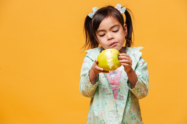 Little girl child eating apple.