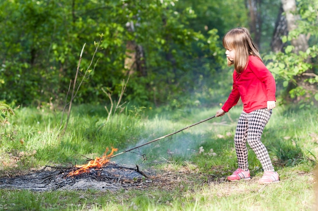 Little girl child in forest playing with bonfire.