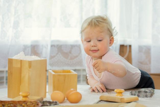 小さな女の子の子供は、祖母がクッキーの生地を準備するのを手伝います。