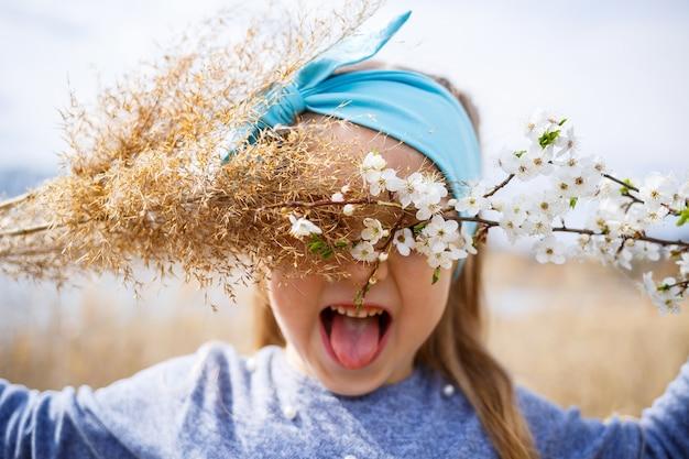 어린 소녀는 마른 갈대와 작은 흰색 꽃이 손에 든 가지, 화창한 봄 날씨, 아이의 미소, 기쁨을 들고 있습니다