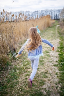 Little girl child holds dry reeds in his hands and runs along a forest trail, sunny spring weather, smilling and joy of the child