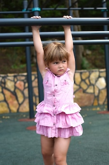 Little girl child on a horizontal bar on a sports ground