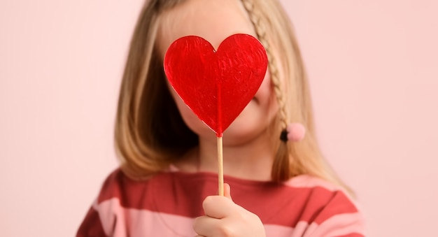 Маленькая девочка в шляпе, держащая красную конфету в форме сердца, посылает воздушный поцелуй на день святого валентина