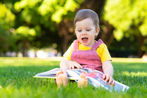 Little girl child is studying a book early toddler development delight baby outdoors in the park