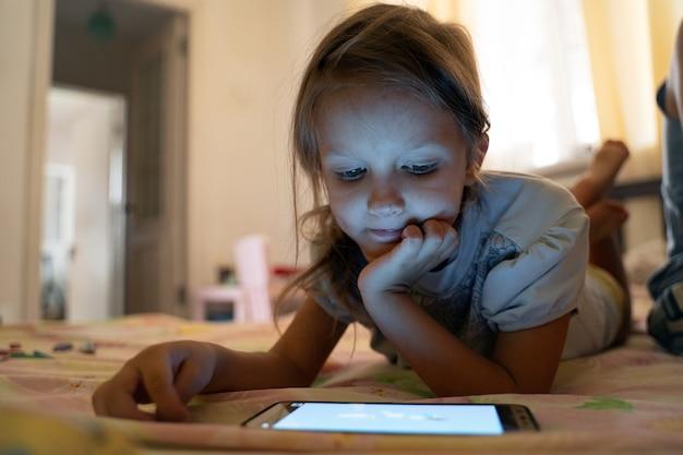 小さな女児は自宅のベッドに横になり、スマートフォンを使用しています