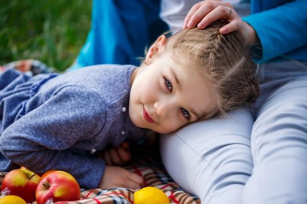 Маленькая девочка лежит на покрывале, зеленая трава в поле, солнечная весенняя погода, улыбка и радость ребенка, голубое небо с облаками