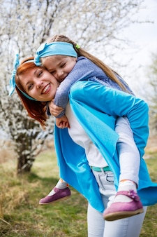 Little girl child and mother woman walks through the spring forest with flowering trees, laugh and play, the beginning of spring, family vacation, love of parents