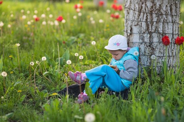 Маленькая девочка играет на ноге смартфона в ногу в поле с зеленой травой и цветущими тюльпанами