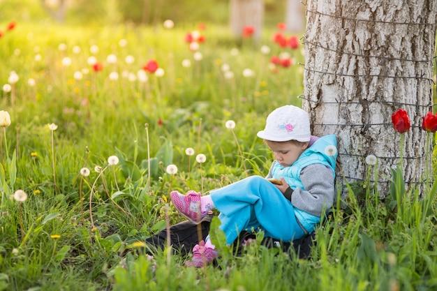 小さな女の子の子供は、緑の草と咲くチューリップのあるフィールドでスマートフォンの脚から脚まで遊んでいます