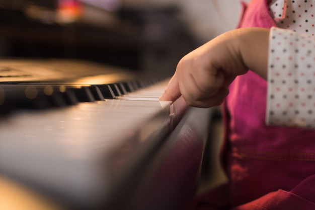 어린 소녀 아이는 집에서 그녀의 방에서 피아노 신디사이저를 연주합니다