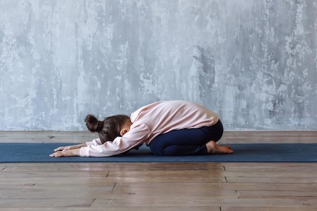 Маленькая девочка, практикующая расслабляющую позу йоги на коврике