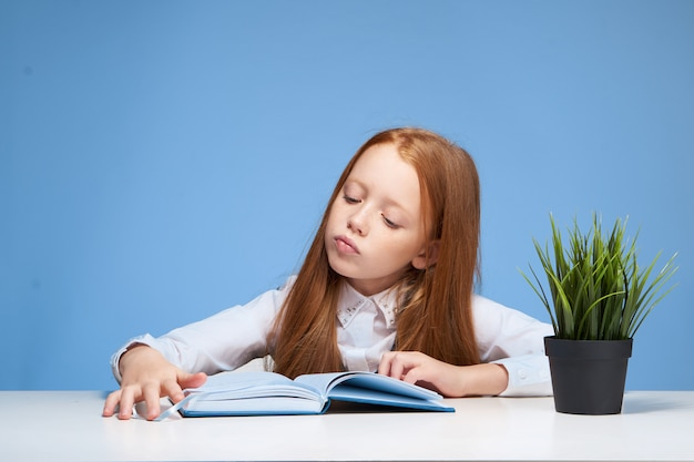 Маленькая девочка ребенок школьница делает домашнее задание, сидя за столом