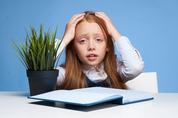 テーブルに座って宿題をしている小さな女の子子供女子高生
