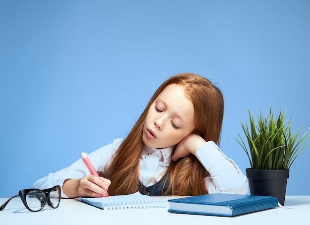 Маленькая девочка ребенка школьница делает домашнее задание, сидя за столом
