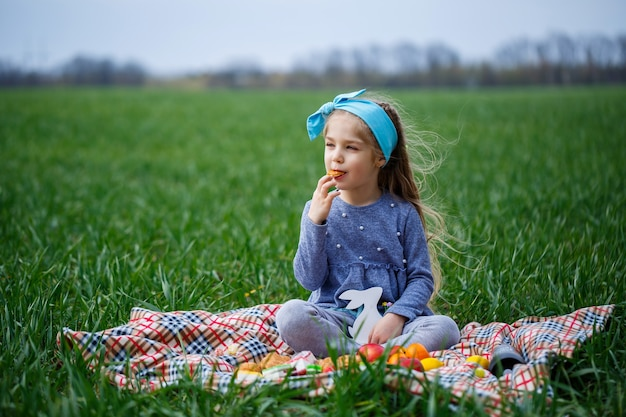 Little girl child sits on the bedspread and eats cookies and marmalade, green grass in the field, sunny spring weather, smile and joy of the child, blue sky with clouds