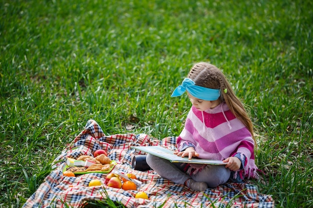 Little girl child sits on a bedspread and reads a book with a fairy tale, green grass in the field, sunny spring weather, smile and joy of the child, blue sky with clouds