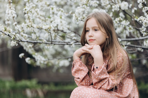 A little girl child sits in the garden under a flowering tree, resting her head on her hands and looking into the distance with a thoughtful look.