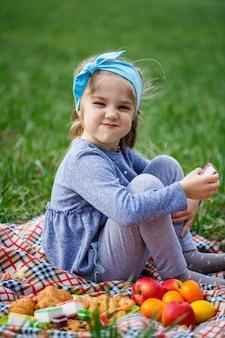 Маленькая девочка сидит на покрывале и ест печенье и мармелад, зеленая трава в поле, солнечная весенняя погода, улыбка и радость ребенка, голубое небо с облаками