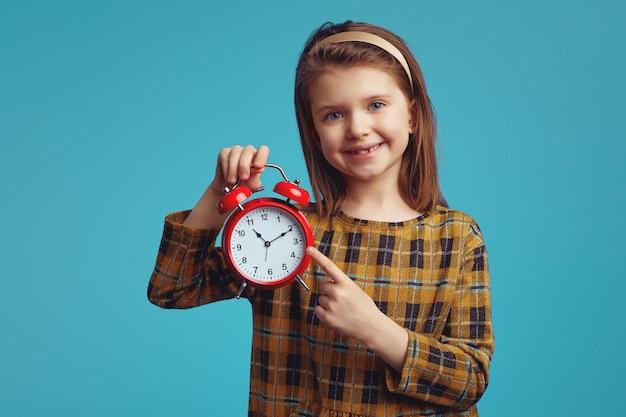 Маленькая девочка улыбается и указывает на будильник, изолированный над синим