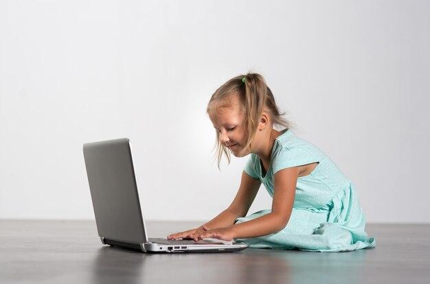 회색 배경에 노트북과 어린 소녀 아이