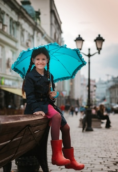 Little girl  child with an umbrella in rubber boots having fun on a bench in the center of moscow