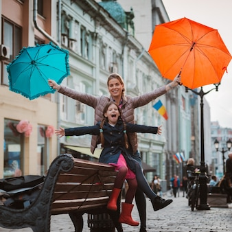 Little girl  child with an umbrella in rubber boots having fun with her mother on a bench in the center of moscow