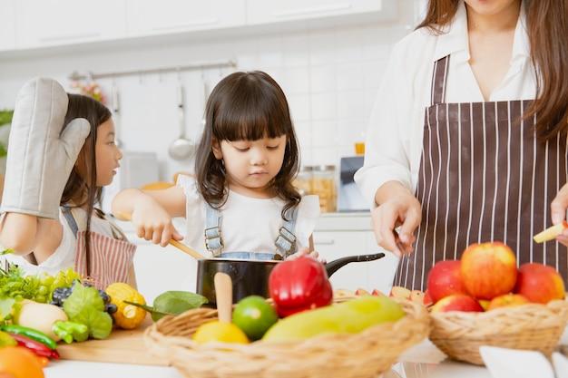 小さな女の子の子供たちは、家庭の台所の休日にママと姉と一緒に料理を楽しんでいます