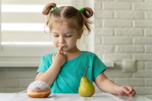 어린 소녀는 도넛과 과일 중에서 선택합니다.