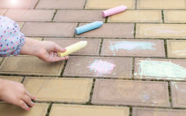 Little girl chooses chalk to draw on the pavement, sidewalk. active kids games