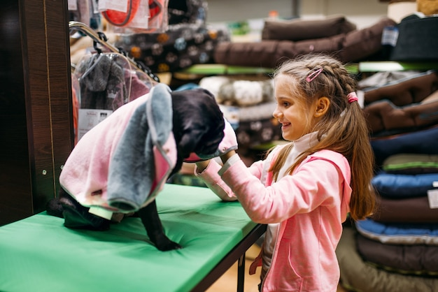Little girl chooses clothes for puppy in pet shop. kid customer buying dogs overall in petshop, goods for domestic animals