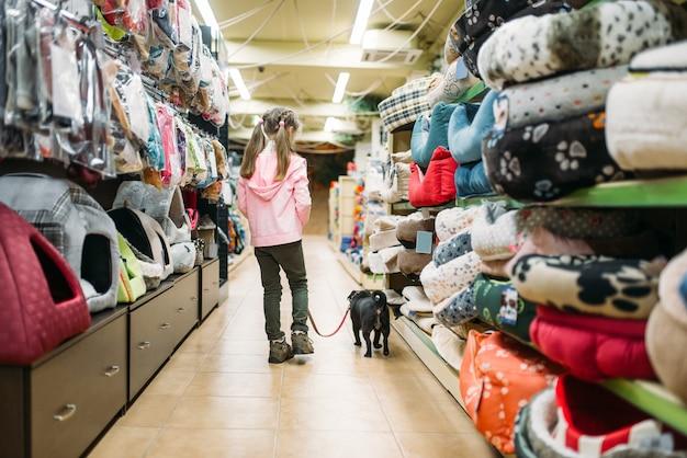 Маленькая девочка выбирает дом для щенка в зоомагазине