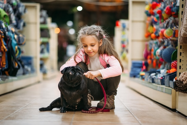 Little girl chooses house for puppy in pet shop
