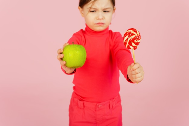Little girl chooses between a lollipop and a green apple. the concept of proper nutrition. a child in a pink wall holds a sweet of sugar in his hand and an apple. difficulty of choice