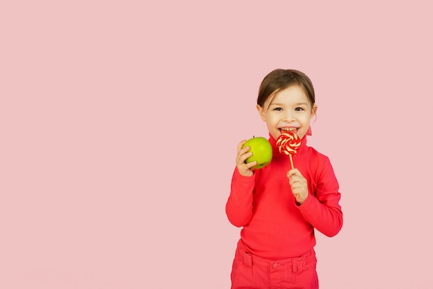 Little girl chooses between a lollipop and a green apple. the concept of proper nutrition. difficulty of choice
