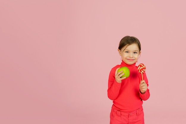 Little girl chooses between a lollipop and a green apple. the concept of proper nutrition.