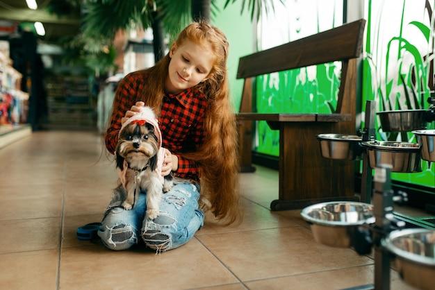 ペット ショップで犬の服を選ぶ少女。ペットショップで子供を買う道具、家畜のアクセサリー
