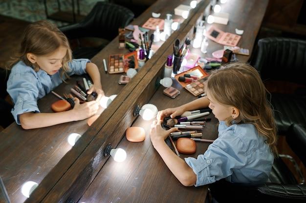 메이크업 살롱에서 거울에 화장품을 선택하는 어린 소녀