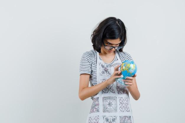 Маленькая девочка, выбирая глобус школы назначения в футболке, фартуке,