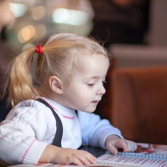 Маленькая девочка, выбирая foood из меню в кафе
