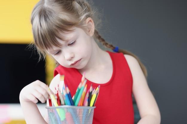 어린이 개념을 위한 유리 미술 수업에서 여러 색연필을 선택하는 어린 소녀