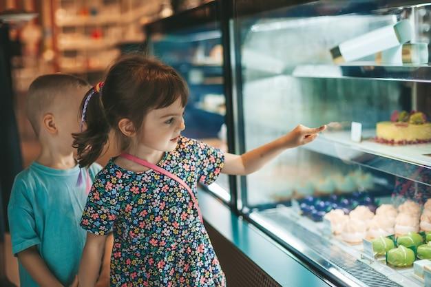 カフェでペストリーを選ぶ少女パン屋のディスプレイでケーキを見ている少年と少女