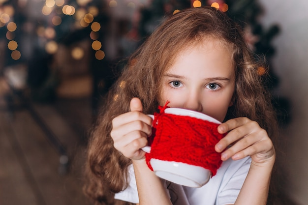 Little girl in christmas decoration with tea at cozy home with colorful new year lights