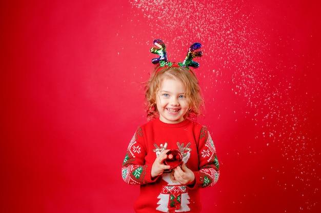 Little girl christmas deer horns red background, new year.