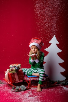 Little girl in christmas pajamas or elf costume and santa hat catches snow sitting on a sled