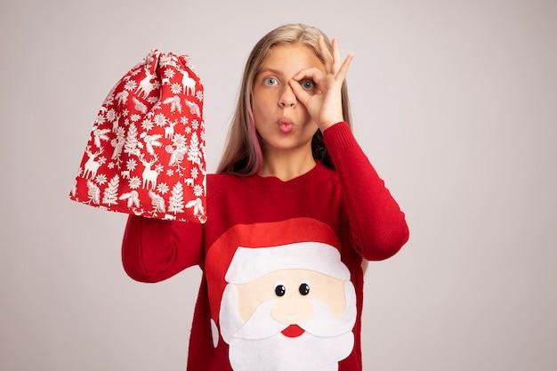 Bambina in maglione di natale che tiene la borsa rossa di santa con regali guardando la telecamera sorpresa facendo segno ok sopra il suo occhio in piedi su sfondo bianco